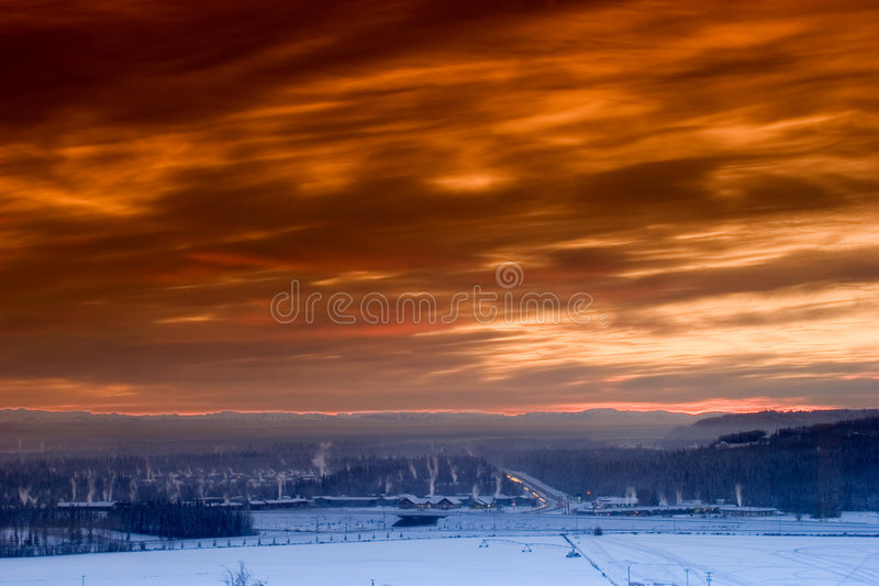 Sunset over frozen town royalty free stock image