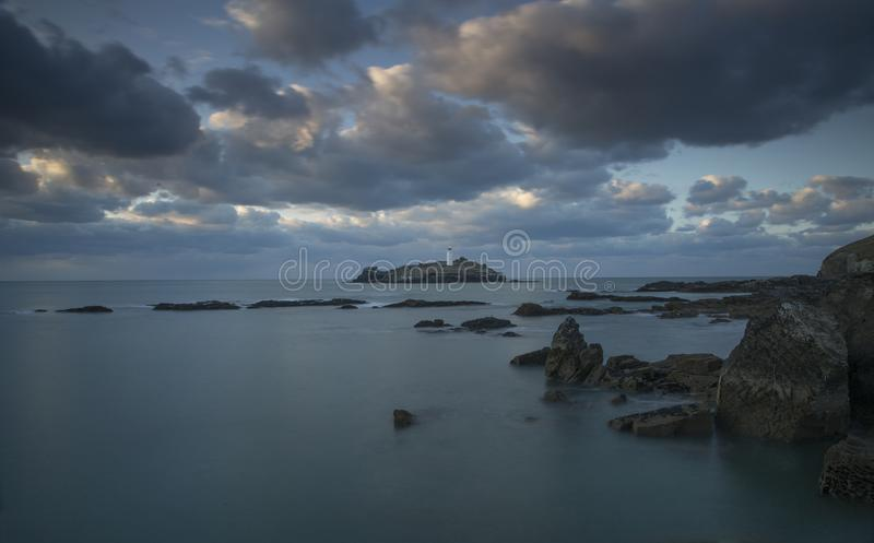 Sunset over Godrevy Lighthouse on Godrevy Island in St Ives Bay with the beach and rocks in foreground, Cornwall uk royalty free stock photo