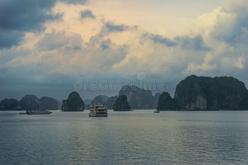 Sunset over Ha Long Bay with cruise boats on the water royalty free stock image