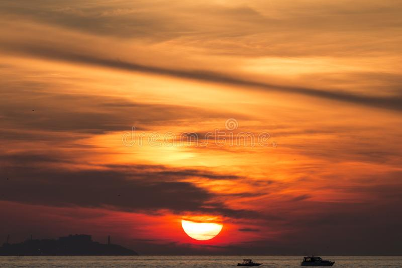 Sunset. Over a highly-populated city, accentuated by dust particles. Very clear and bright perspective with clouds layers that accentuate the horizon, while royalty free stock photo