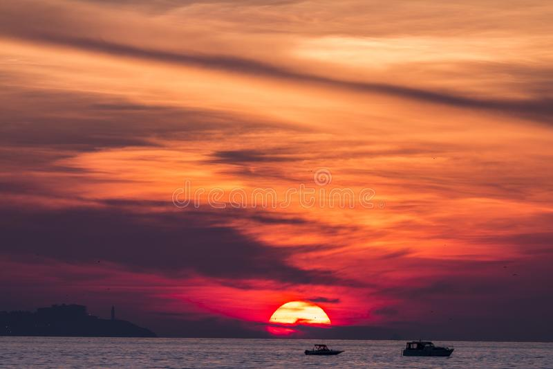Sunset. Over a highly-populated city, accentuated by dust particles. Very clear and bright perspective with clouds layers that accentuate the horizon, while royalty free stock photos