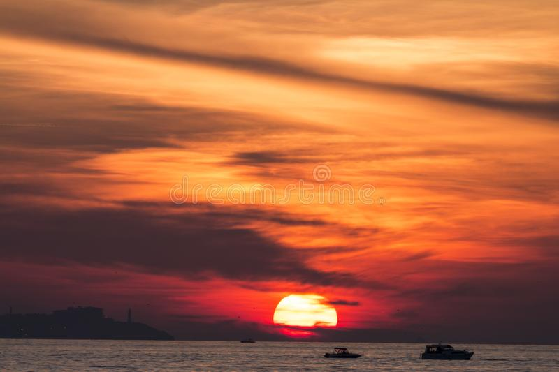 Sunset. Over a highly-populated city, accentuated by dust particles. Very clear and bright perspective with clouds layers that accentuate the horizon, while royalty free stock images