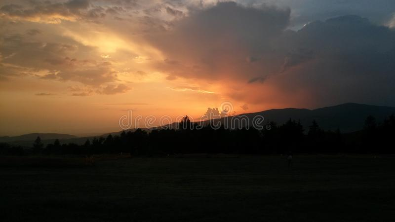 Sunset over the hills and forest royalty free stock photography