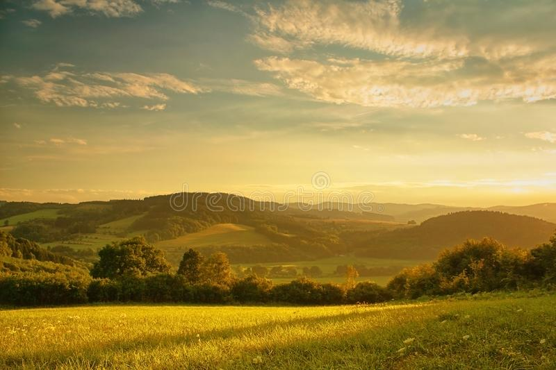 Hilly landscape in the setting sun, meadow in the foreground royalty free stock photos