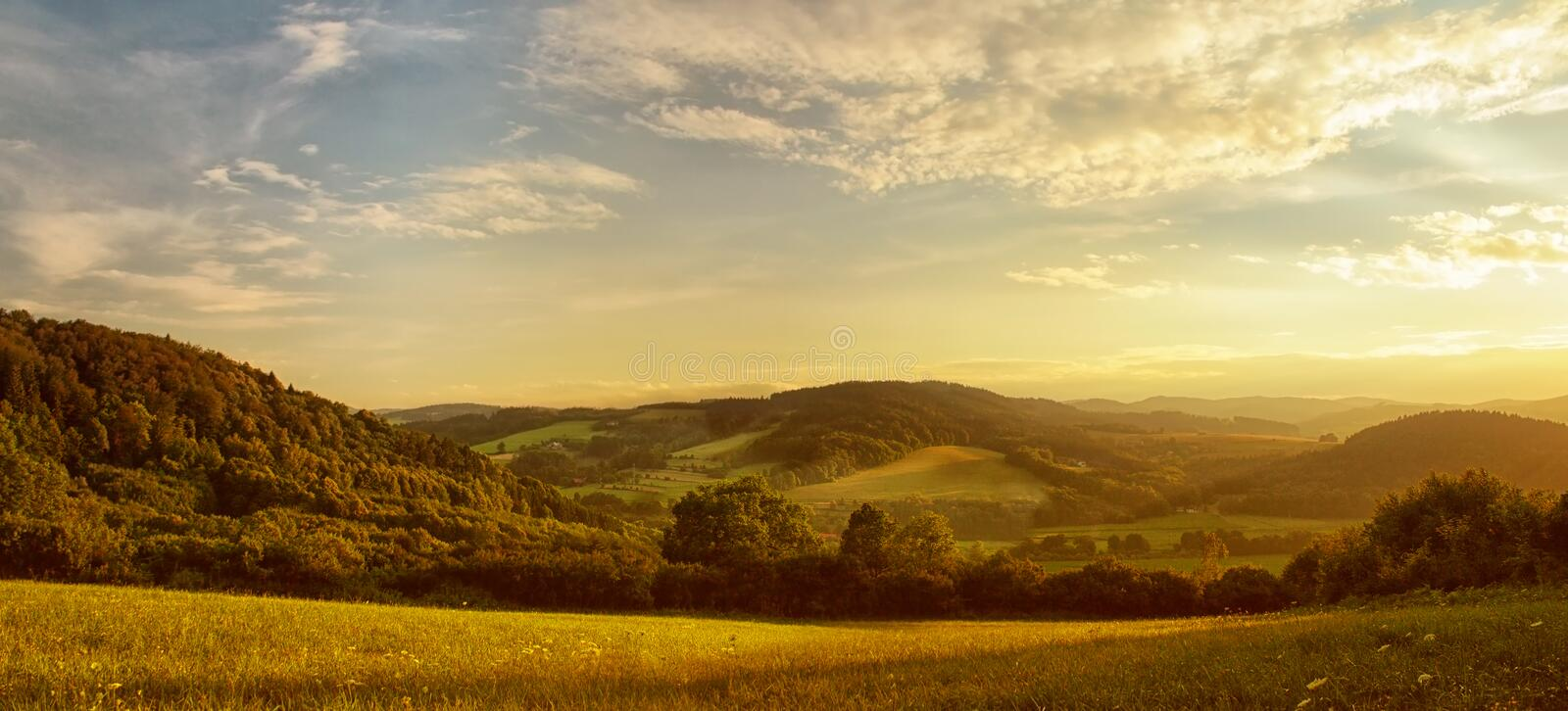 Sunset over hilly landscape, the golden glow of the setting sun, meadow in the foreground - scenic panorama royalty free stock image