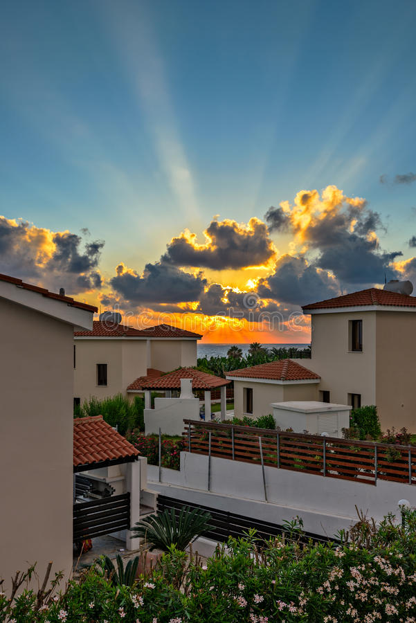 Sunset over holiday beach villas. Sunset with sunbeams over luxurious holiday beach villas for rent on Cyprus stock images