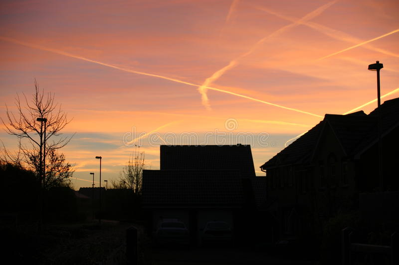 Sunset over houses with aircraft contrails. Sunset over houses with trees, street lights and aircraft contrails crossing the sky royalty free stock photos
