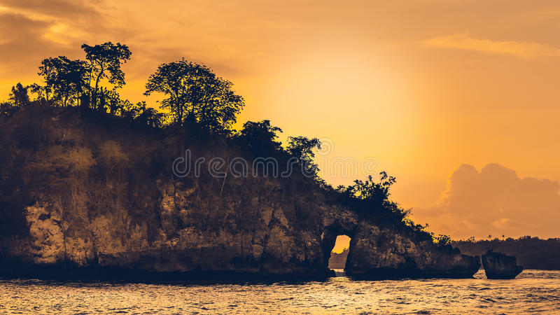 Sunset over the Huge Rock on Beautiful Crystal Bay in Nusa Penida Bali stock photos