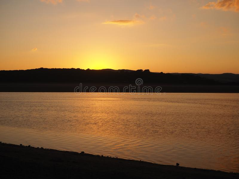 Sunset over the Kent Estuary at Arnside, Cumbria. Beautiful glow as the sun sets behind the Cumbrian hills over the Kent Estuary at Arnside, England royalty free stock photo