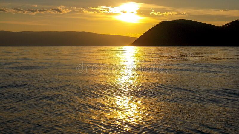 Sunset over lake Baikal and its shores. The sunset over the spurs of Khamar-Daban ridge, the eastern slope of the southern part of Seaside ridge, and lake royalty free stock photos