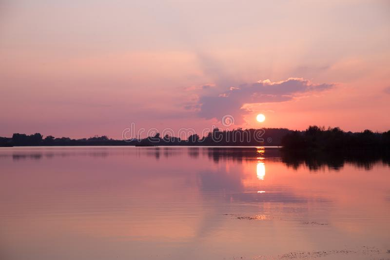 Sunset over the lake in colors of pink and purple stock photo