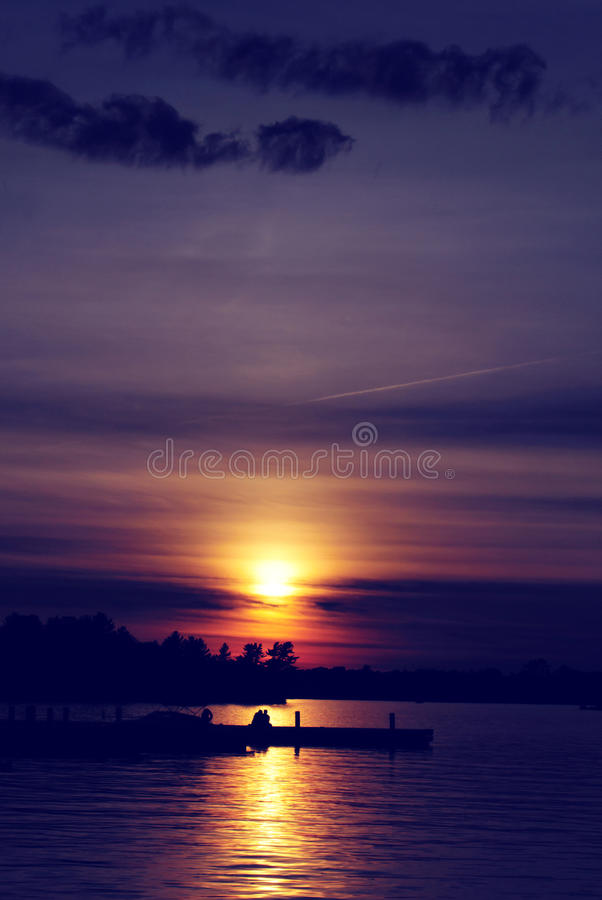 Sunset Over a Lake with Couple - Vertical. The sun is setting over a lake with a silhouette of a couple sitting on the dock. Silhouetted trees are seen against royalty free stock photo