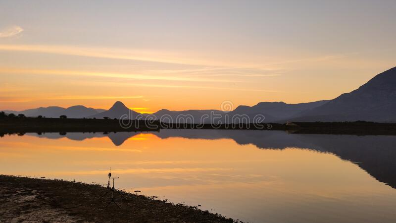 Sunset over a lake with mountains in the background stock photography