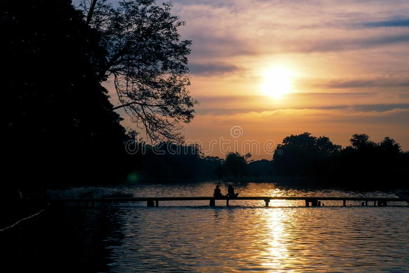 Sunset over the lake .silhouette photography. Romantic moment. Couple on the bridge stock images