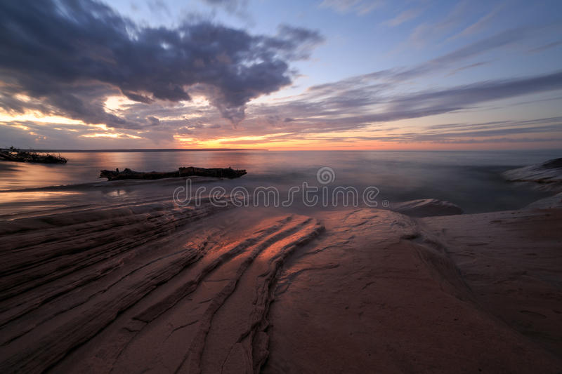 Sunset over Lake Superior at Pictured Rocks, Michigan. A vivid sunset lights up the rocky shores of Miners Beach in the Upper Peninsula of Michigan. Miners Beach stock photography