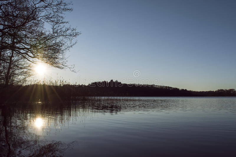 Sunset over a lake in winter. Sun setting, spreading its' rays, over a lake in winter stock photos