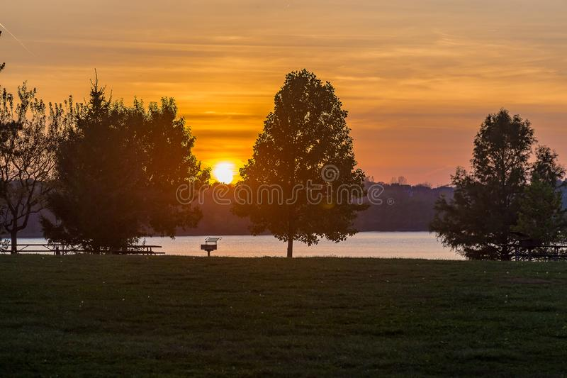 Sunset over lake Zorinsky Omaha Nebraska USA. Silhouetting two trees. Colorful fiery sky as background royalty free stock photography