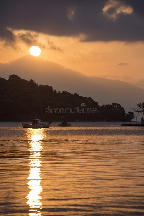 Sunset over Madouri, Lefkada, Greece. Scenic landscape at tourist viewpoint. Fishing boat stock photo