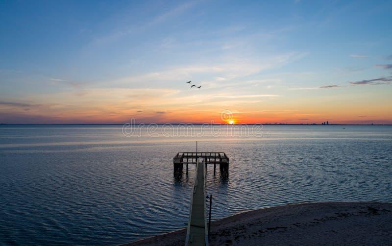 Sunset over Mobile Bay on the Alabama Gulf Coast beach royalty free stock image