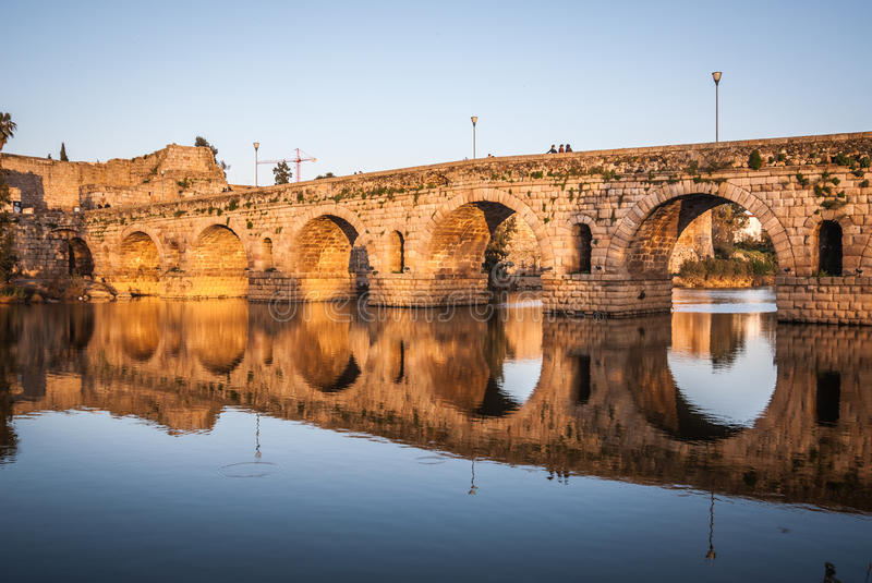 Sunset over the monument, Roman bridge over the Guadiana River in Merida, Spain royalty free stock photography