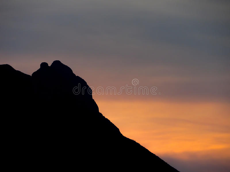 Sunset over Mountain. Bright yellow sunset over Cerro de la Silla mountain, at Monterrey, Mexico stock photo