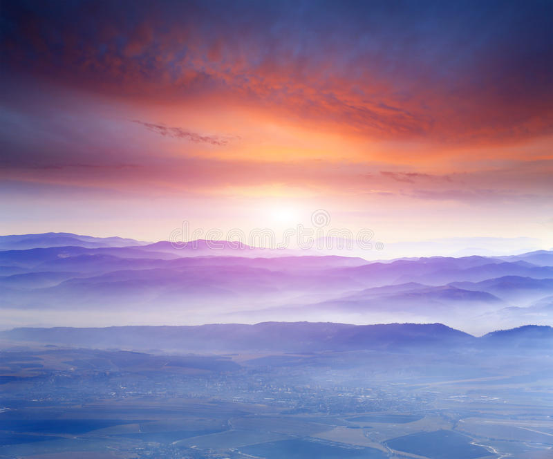 Sunset over mountains. Landscape with sunset over cloudy mountains stock photography