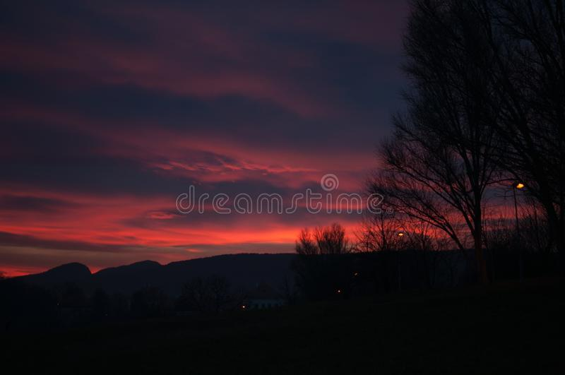 Sunset over Mountains. Night dark blue and pink sky and silhouette of trees royalty free stock photo