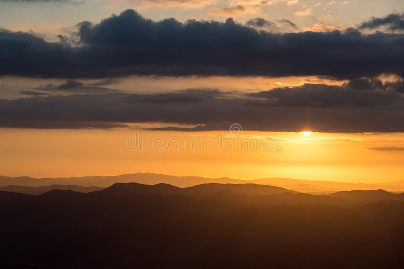 Sunset over mountains range in Umbria, with sun coming down behind some clouds stock photos
