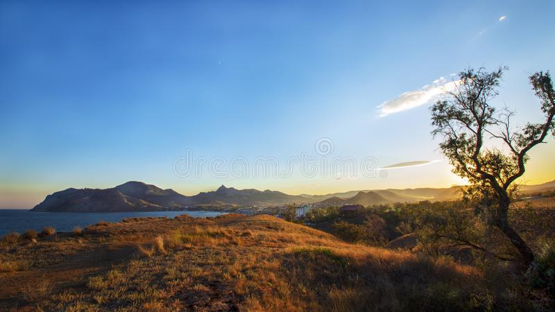 Sunset over the mountains and the sea royalty free stock photos
