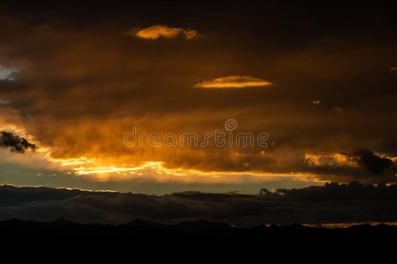 Sunset over mountains. With storms clouds outdoor morning sunrise dark scenic dramatic orange landscape background panoramic thunderstorm danger stormy nature royalty free stock photography