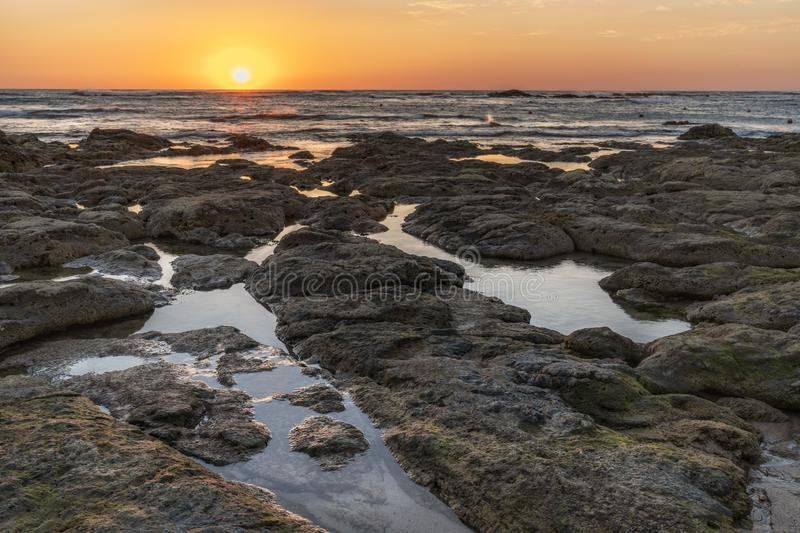 Sunset over the ocean with breaking waves. Along a rocky coastline royalty free stock photography