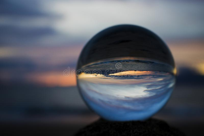 Sunset over Ocean with Island in Silhouette in Glass Ball royalty free stock photos