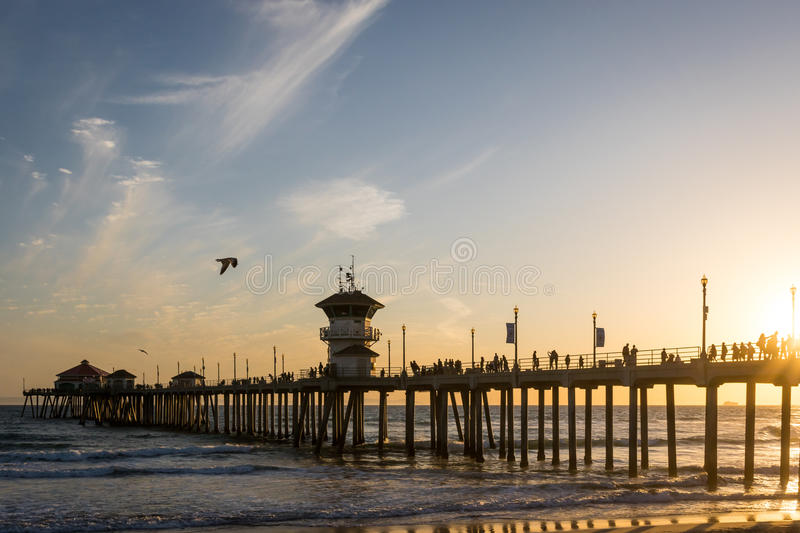Sunset over Ocean Pier with Bird Flying Overhead. Golden Sunset over ocean pier with bird flying overhead. Taken in Huntington Beach, California in Orange County royalty free stock photography