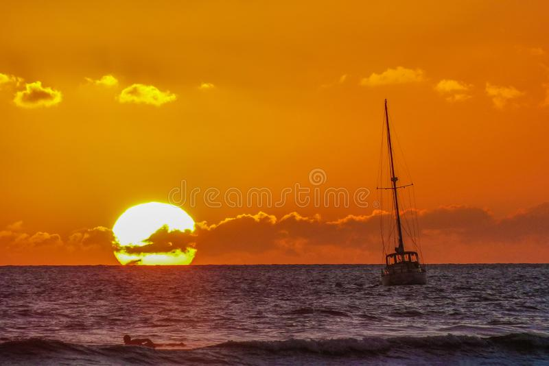 Sunset Over the Ocean with Sail Boat and Surfer in Maui HawaiiSunset. Sunset Over the Ocean in Maui Hawaii with a Sail Boat and a Surfer Paddling Out in Maui royalty free stock photo