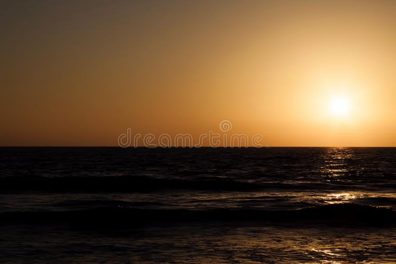 Sunset Golden Sky Over Dark Ocean Waves royalty free stock photos