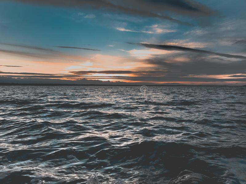Sunset over ocean waves stock images
