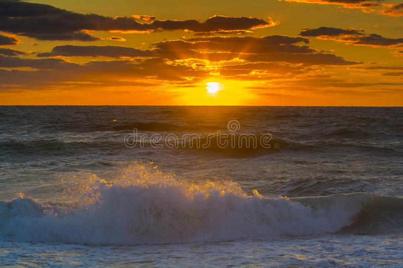 Sunset over the ocean with waves. Orange sunset over ocean with waves rolling in splashing on the sandy beach royalty free stock photography