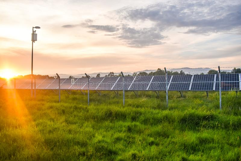 Sunset over a photovoltaic power plant with photovoltaic modules for renewable energy on the field. Solar power generation royalty free stock image