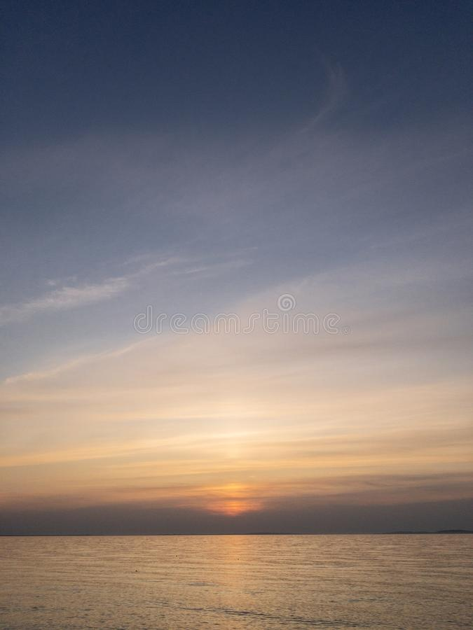 Sunset over quiet sea with sun hiding behind clouds. Crimean seascape copy space. Vertical stock image