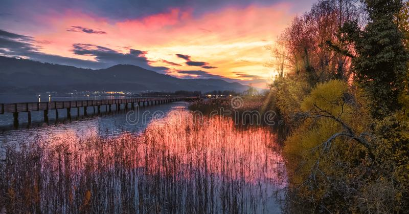 Sunset over the rich marshlands on the shores of the Upper Zurich lake Obersee along the wooden bridge, Rapperswil-Jona, Sankt stock photo