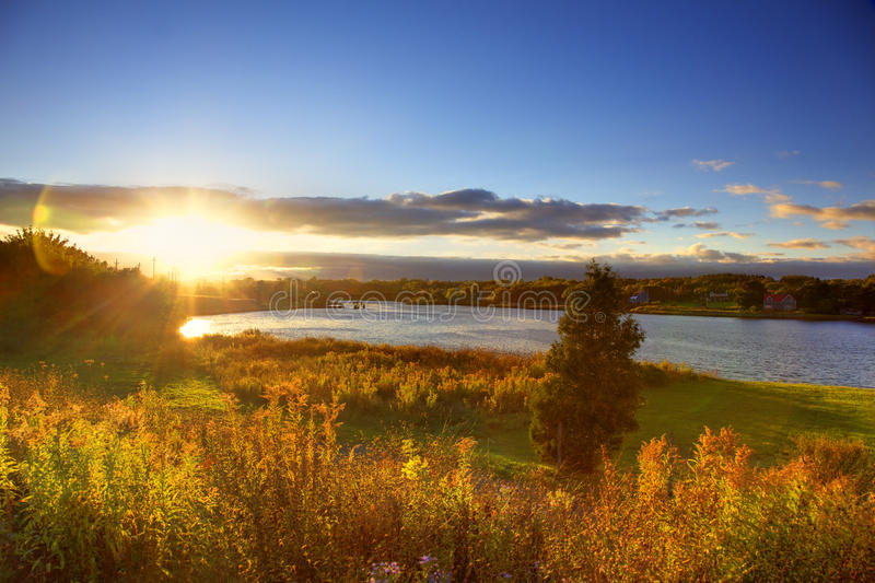 Sunset over river in autumn. Beautiful sunset over river with autumn trees in foreground, Sydney, Nova Scotia, Canada stock images