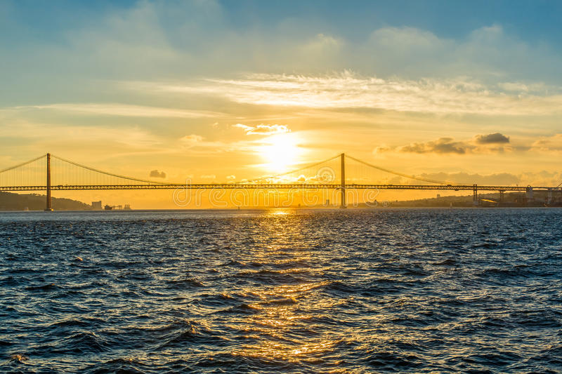 Sunset over the river and the bridge Twenty fifth April stock photo