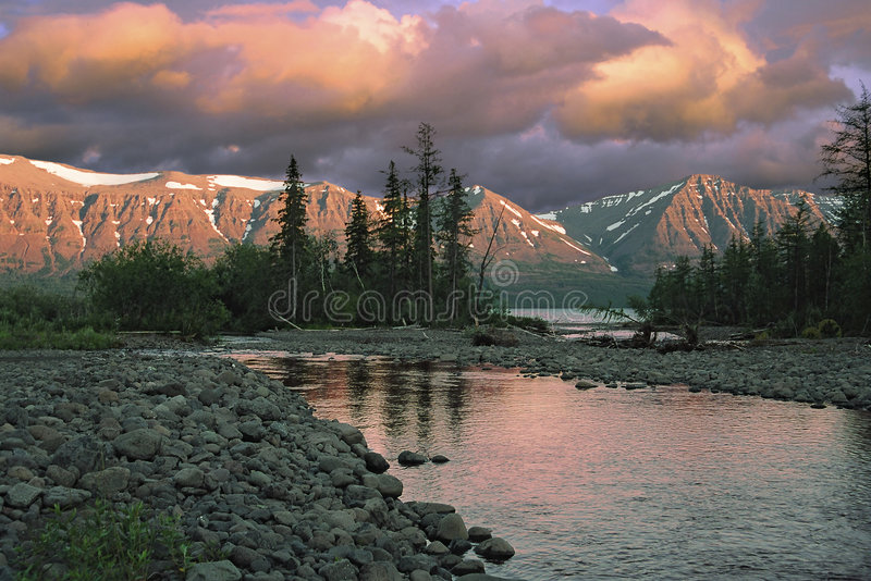 Sunset over river and mountains stock photos