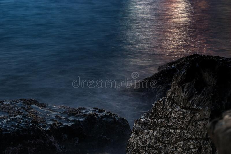 Sunset over rocks on coastline royalty free stock image