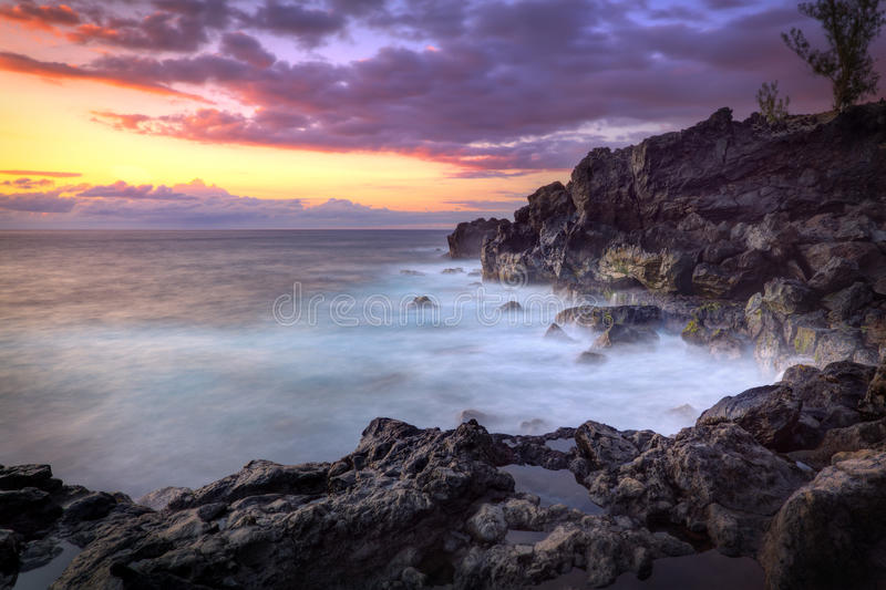 Sunset over rocky coastline. Scenic view of golden sunset and cloudscape over rocky coastline with waves breaking in foreground, Saint-Leu, Reunion Island royalty free stock image