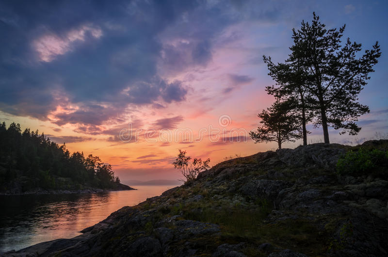 Sunset over rocky lake shores. Vivid colors of sunset over rocky lake shores stock photography