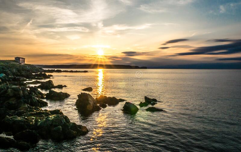 Sunset over rocky ocean coastline stock photo