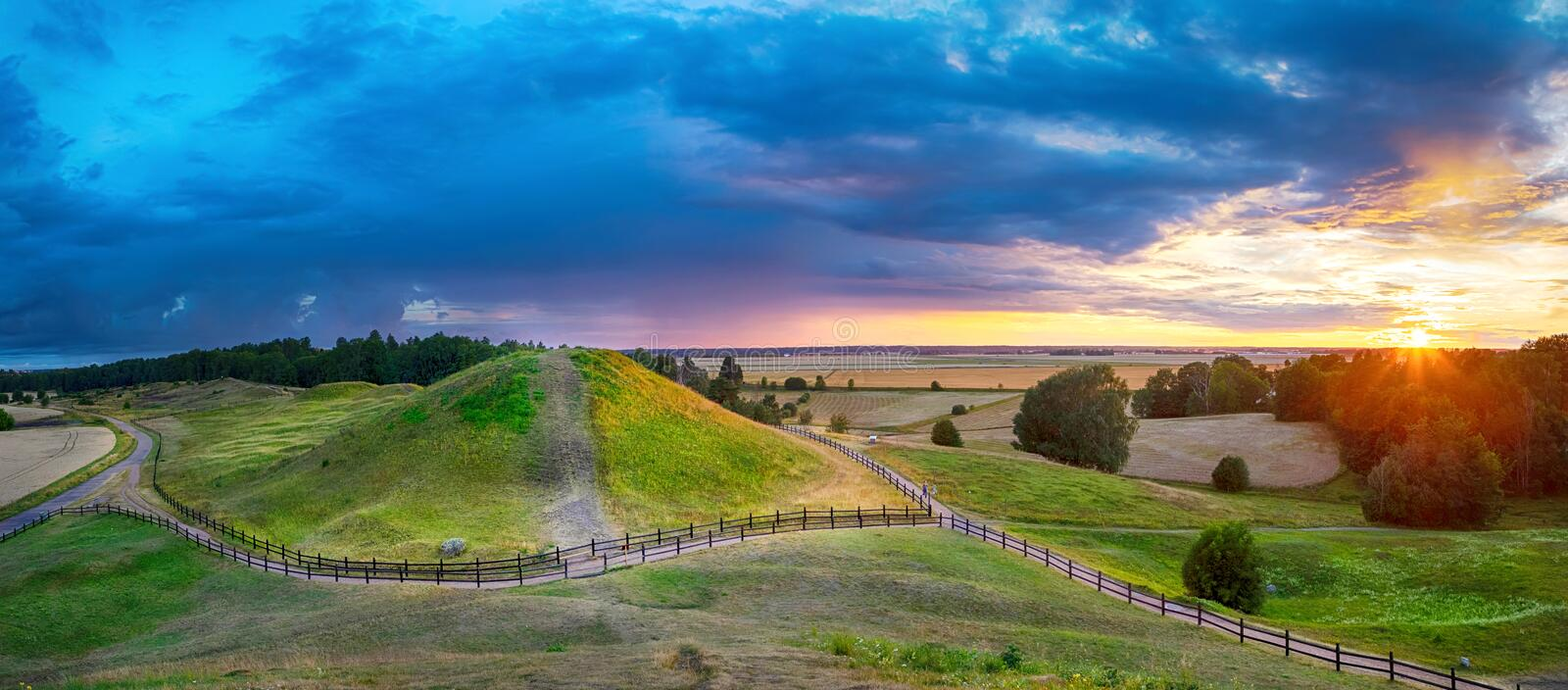 Sunset over Royal Mounds in Uppsala, Sweden. Sunset over Royal Mounds in Gamla Uppsala, Uppland, Sweden HDR panorama royalty free stock image