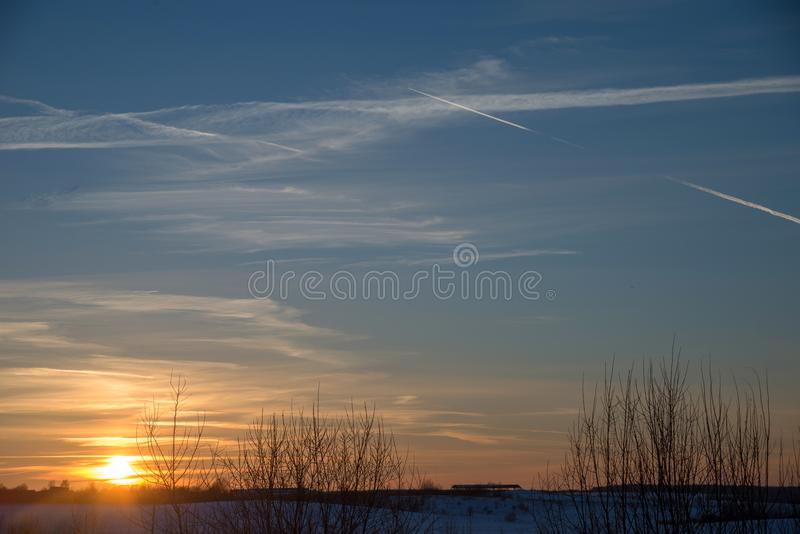 Sunset over village in winter royalty free stock photography