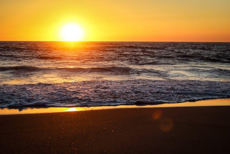 Sunset over sandy beach stock photo